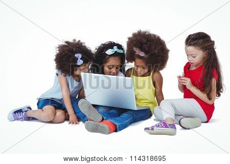 Cute girls sitting on the floor using laptop on white screen