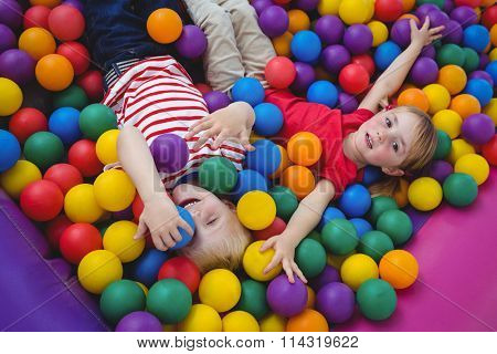 Cute smiling kids in sponge ball pool looking at camera