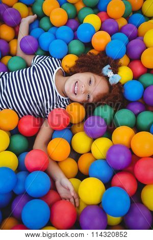 Cute smiling girl in sponge ball pool looking at camera