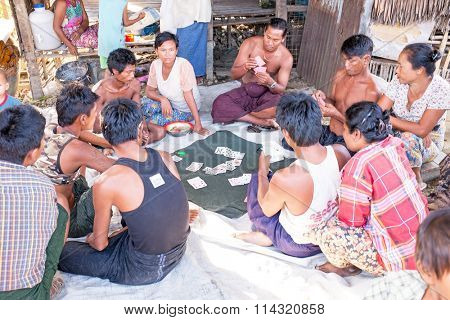YANGON, MYANMAR - November 25, 2015: Villagers playing cards in the countryside from Myanmar.