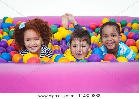 Cute smiling kids in sponge ball pool looking at camera