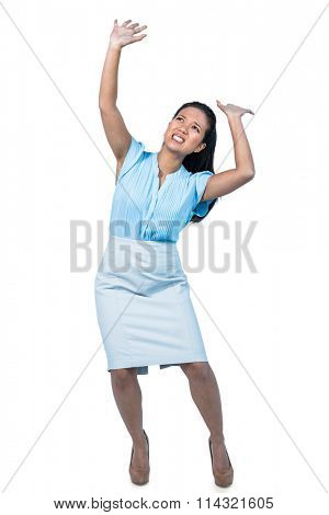 Scared young businesswoman holding something against white background