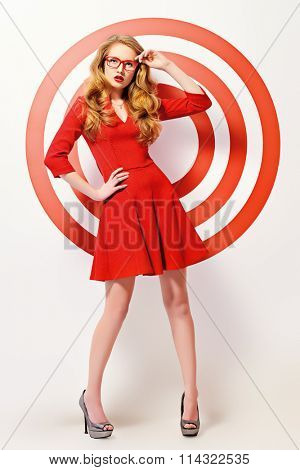 Gorgeous fashion model in red dress and elegant red glasses posing over red circles of the target. Beauty, fashion. Optics, eyewear. Full length portrait.