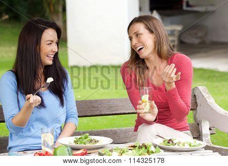 Two Women Friends Sitting Outside In Garden Having Lunch