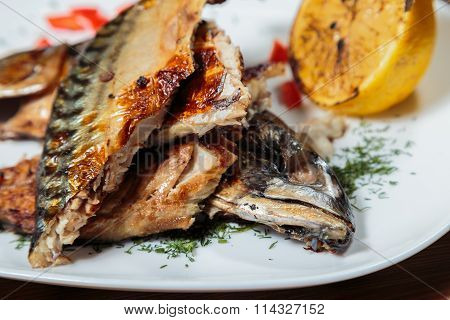 Smoked mackerel with vegetables grilled on a white plate.