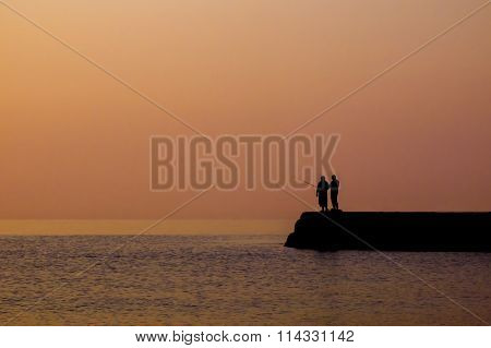 Silhouette of fishermen against the sky at sunrise