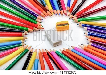 Heart Shape Made Out Of Pencils With Eraser And Pencil Sharpener In The Middle On White Background