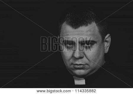 Black and white photography priest on a dark background.