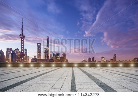 empty marble floor and cityscape in colorful sky at dawn