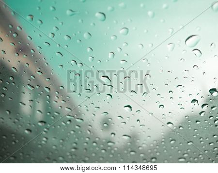 Raindrops On Car's Glass With Blurry Cloudy Sky In Village. Green Color Tone.