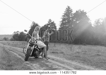 Black and white photo biker couple on a motorcycle in the field