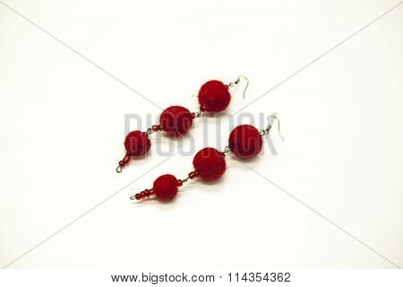 Beautiful hand-made earrings felted wool sheep red shades on a white background, close-up