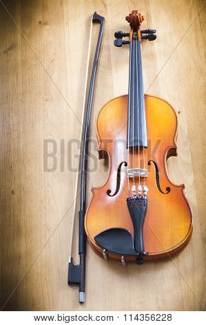 violin with a fiddlestick on a wooden background