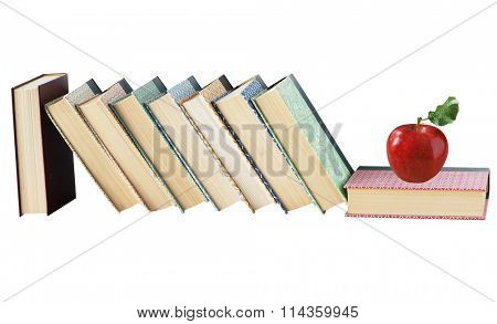 Old books and fresh red apple isolated on white background