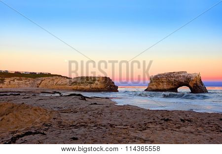 Sea arch formed by wave erosion at Natural Bridges State park at the sunset