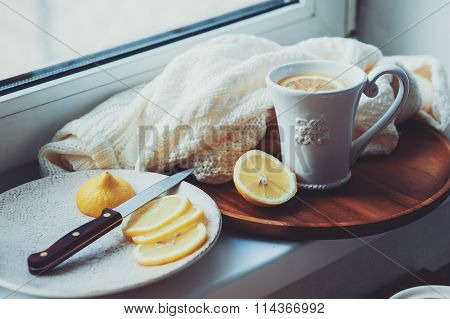 tea with lemon slices on wooden plate, vintage toned, cozy morning at home