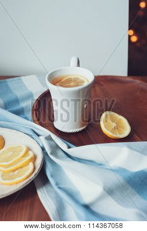 tea with lemon slices on wooden plate ,vintage toned, cozy morning at home