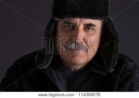 Portrait of mature Caucasian man in fur-cap against dark background
