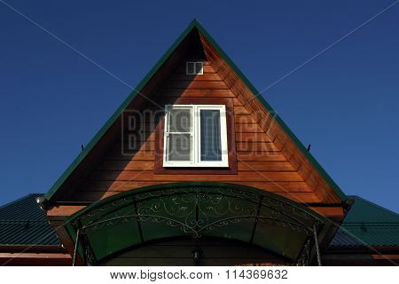 Green Metal Roof  And White Attic Window