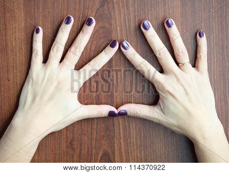 Middle aged woman hands with shellac manicure over wooden background wearing wedding ring