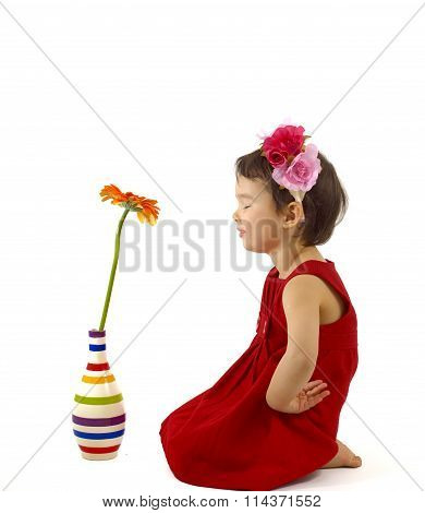 Little Girl In Red Dress Making A Wish In Front Of A Gerbera Flower
