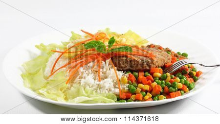 Plate of rice with pork and vegetable