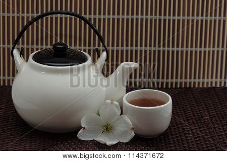 Teapot and cup of tea over bamboo background