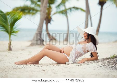 Beautiful Pregnant Woman Lying On  Sandy Beach With Palm Trees