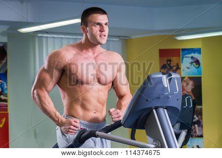 A man on a treadmill. Strong man doing on the treadmill.