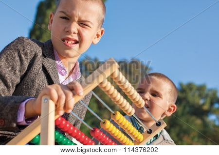 Back to school two confused little boys playing with wooden abacus in the park. One arround seven, the ather four.