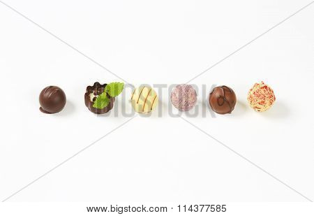 line of assorted belgian chocolate pralines on white background