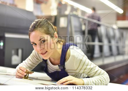 Woman in printing house using magnifying glass