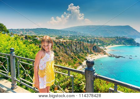 Adorable little girl posing against amazing view of Capo Vaticano, Calabria, Italy