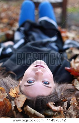 Young Teenage Girl Lying Upside Down On A Bed Of Leaves In Autumn