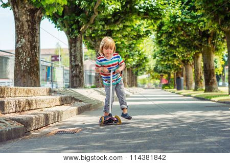 Outdoor portrait of a cute little boy riding scooter in the park