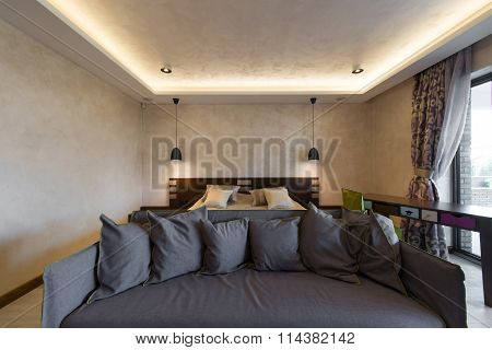 Bedroom with double bed and living room in hotel suite