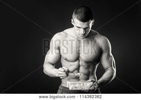 Male bodybuilder posing on a dark background.