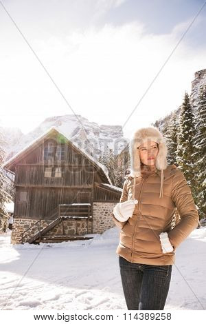 Woman Looking Aside While Standing In Front Of Mountain House
