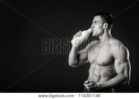 The athlete comparing holding a bottle of milk and beer on a dark background