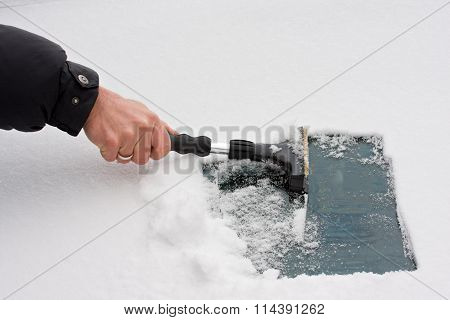 Hand With An Ice Scraper Cleaning A Windshield