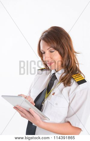 Beautiful woman pilot wearing uniform with epaulettes holding tablet