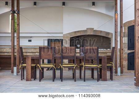 Long table and chairs on veranda in luxury villa exterior