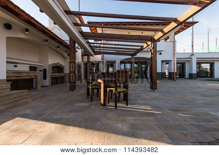 Beautiful terrace lounge with pergola and wooden table with chairs
