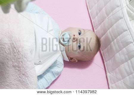 Baby Boy In Cot With Bumper Pad And Pacifier