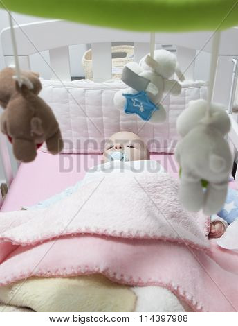 Awake Baby Boy Lying In White Cot With Mobile
