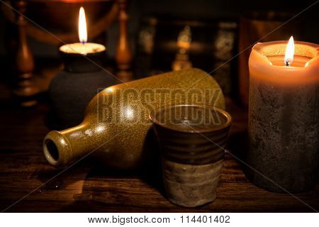 Medieval Background With A Old Bottle, A Mug And Candles