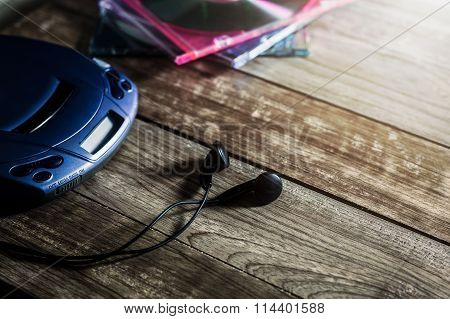 Cd Player With Disc And Earphones On Wooden Plank