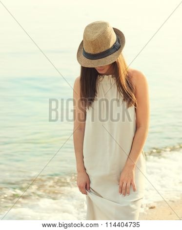 Happy smiling woman walking on a sea beach dressed in white dress and hat covering face, relaxing and enjoy fresh air, outdoor portrait.