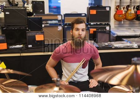 male musician with cymbals at music store