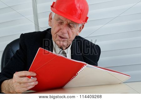 Mature Architect With Red Helemet  Reading
